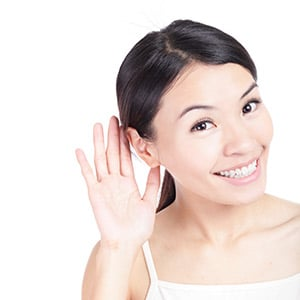 Woman smiling and holding her hand up to her ear
