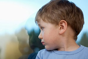 Young boy looking outside window