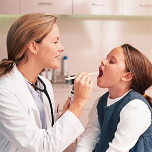 Doctor giving an oral exam to a young girl