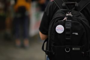 "Button on a backpack that reads ""facts matter"""