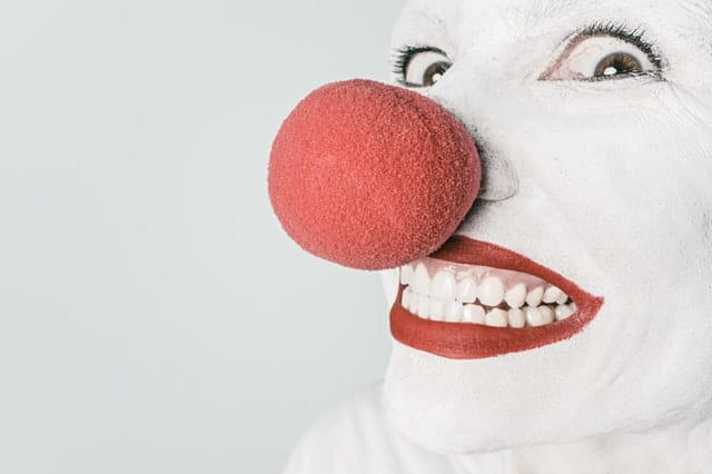 Smiling clown with red ball on nose