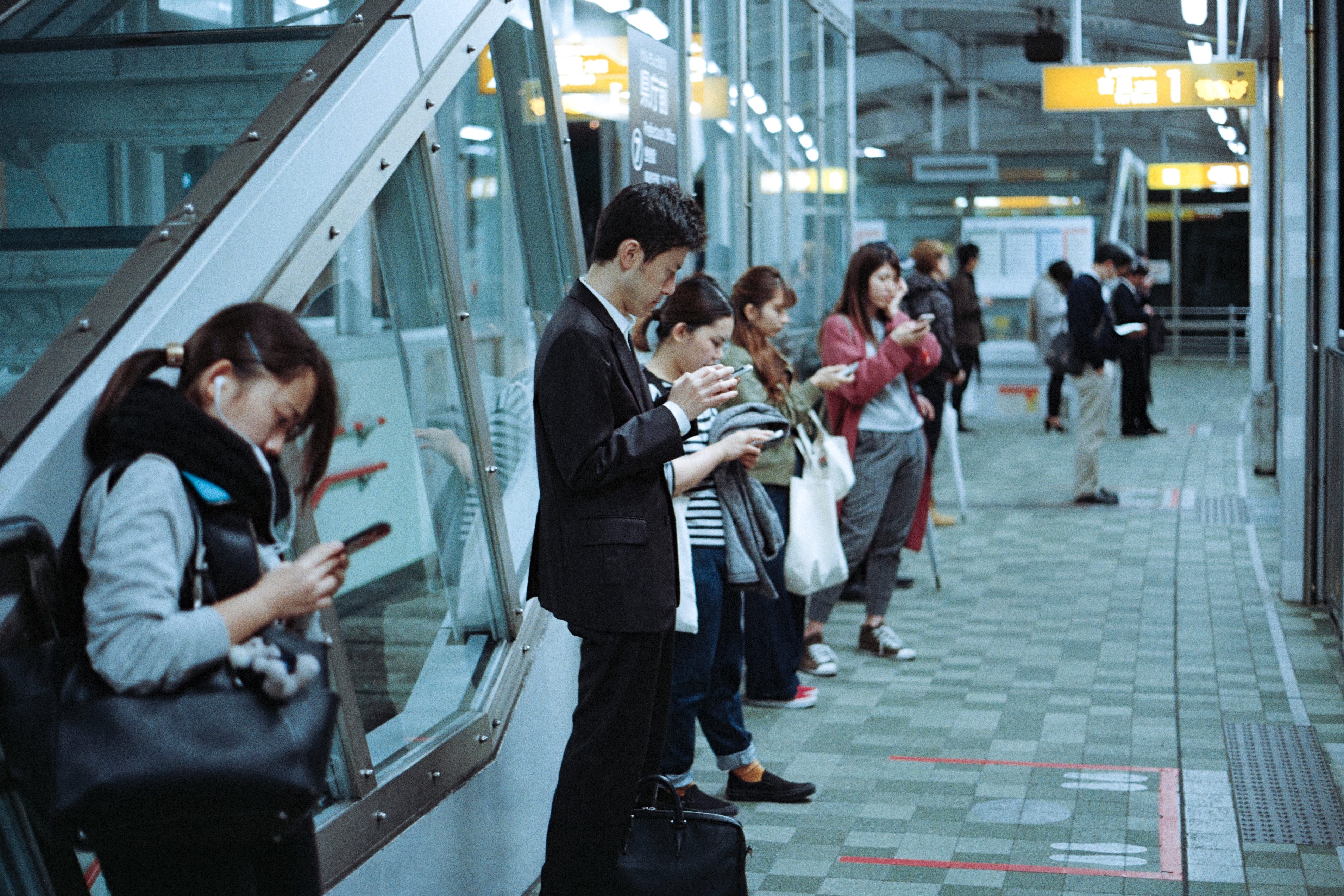 Commuters texting while waiting for the train