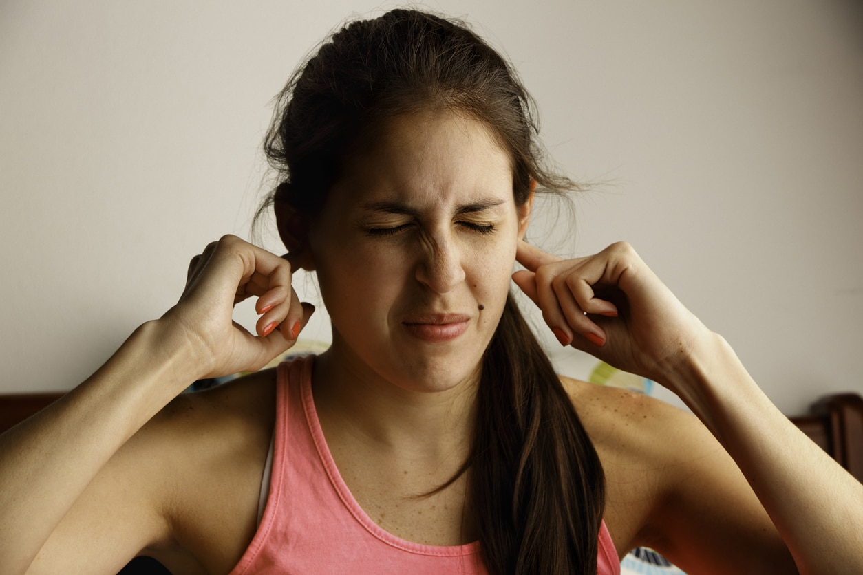 Young woman disturbed by ringing in the ears