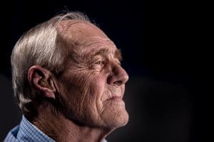 Side shot of an elderly man with a hearing aid