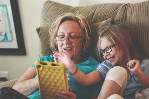 Woman and girl sit in a recliner while playing with a tablet