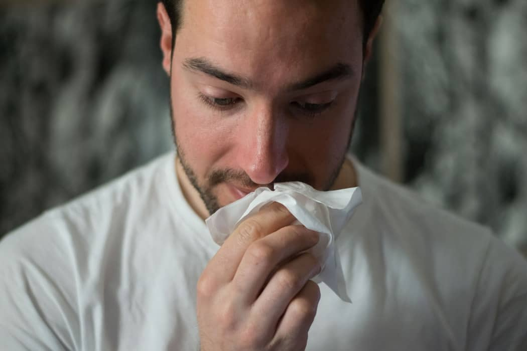 Man coughing into napkin.
